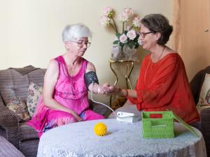 Pflegerin mit Klientin beim Blutdruckmessen im Wohnzimmer.