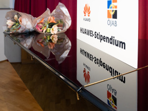 """Tafel """"HUAWEI-Stipendium"""" und Blumen im HIitergrund"""