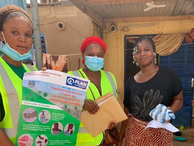Drei Frauen mit einem Infoplakat zum Coronavirus.