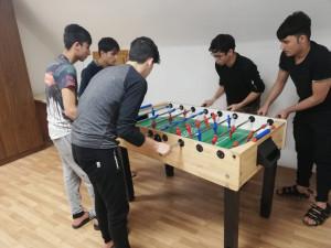 Unbegleitete minderjährige Flüchtlinge spielen zusammen Tischfußball.