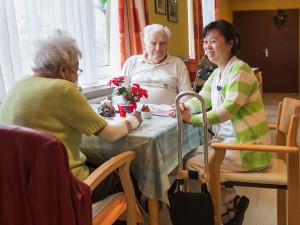 Pflegerin im Gespräch mit zwei BewohnerInnen.